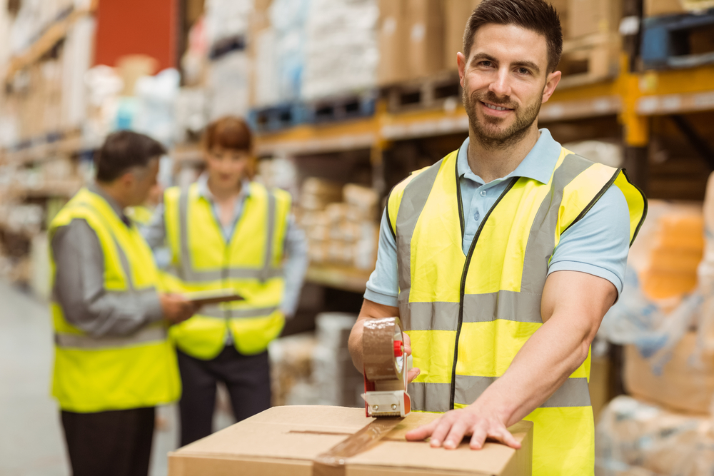 Smiling warehouse workers preparing a shipment in a large warehouse.jpeg